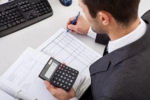 księgowy mężczyzna liczący kalkulator